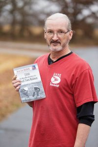 Jesse Lee Hatfield of Conway holds a copy of his book, 72058: The Many Mini Adventures of a Small-Town Mailman, about his experiences as a mail carrier for the Greenbrier Post Office.
