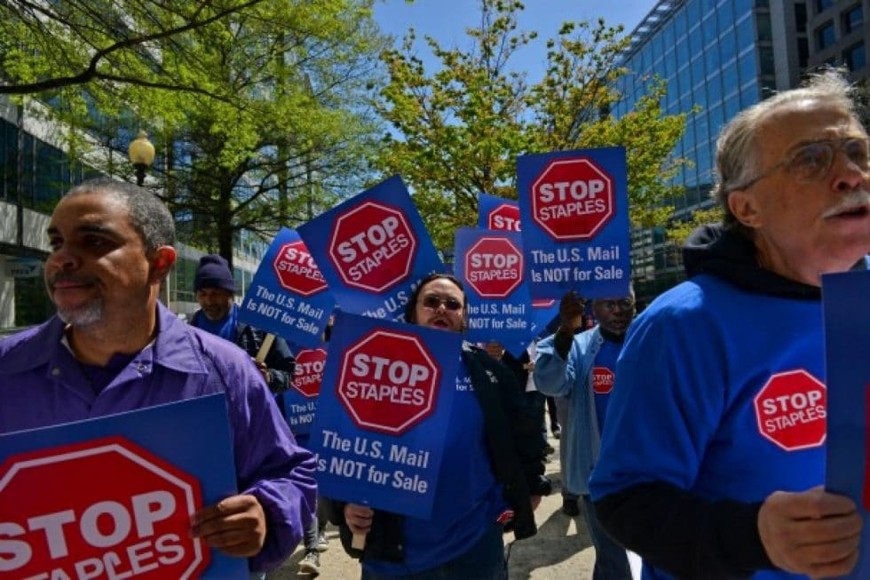 Peter Menge, along with national leaders and local members of the American Postal Workers Union (APWU) make their way from Farragut Square to a Staples' store in Northwest Washington to protest a USPS-Staples deal. (Marlon Correa/The Washington Post)