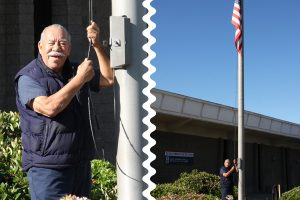 El Cajon CA Building Maintenance Custodian Rudy Renteria lowers the American flag as postal facilities that are open are required to fly the POW-MIA flag on May 30.