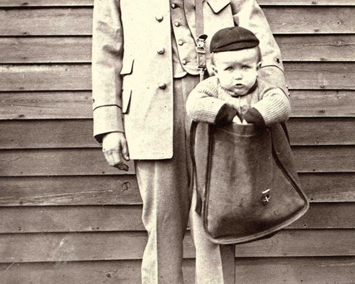 Uniformed Letter Carrier with Child in Mailbag (Smithsonian Institution)