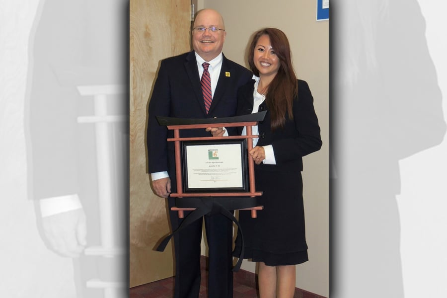 Chief Operating Officer David Williams presents Philadelphia Postmaster Jennifer Vo with her black-belt certification.